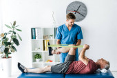 handsome doctor holding leg of mature patient exercising in clinic