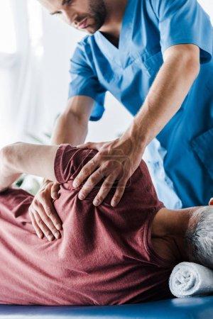 Photo pour Foyer sélectif du médecin touchant l'homme d'âge moyen couché sur la table de massage - image libre de droit