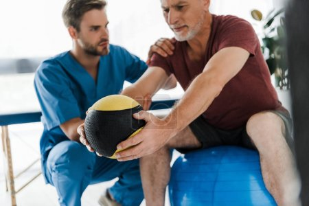 selective focus of mature patient exercising on fitness ball near doctor