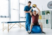 handsome doctor standing near mature man exercising on fitness ball