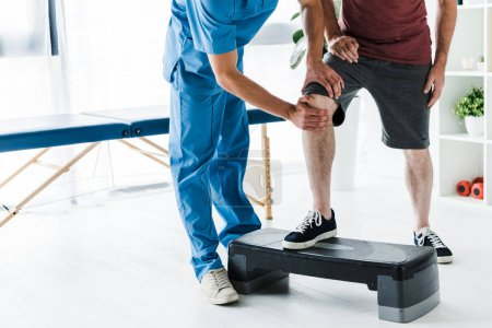 Photo for Cropped view of doctor touching knee of mature patient on step platform - Royalty Free Image
