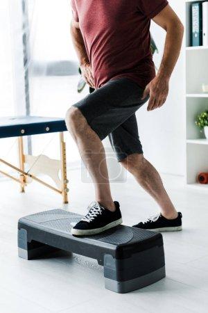 Photo pour Vue recadrée de l'homme âgé moyen exerçant sur la plate-forme d'étape dans la clinique - image libre de droit