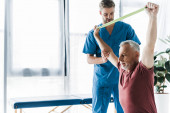 doctor standing near middle aged man exercising with resistance band