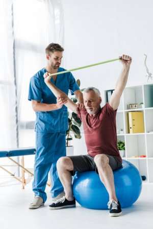 handsome doctor standing near middle aged man exercising with resistance band while sitting on fitness ball