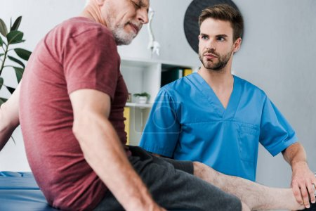 Photo for Selective focus of handsome bearded doctor holding leg on mature patient with pain - Royalty Free Image