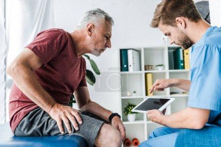 Photo pour Beau médecin pointant avec le doigt à la tablette numérique près du patient - image libre de droit