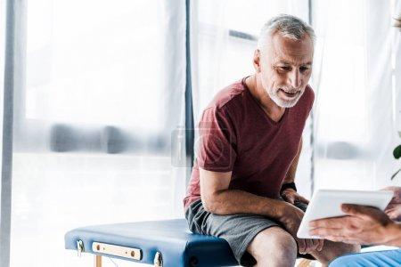 Foto de Vista recortada del médico que sostiene la tableta digital cerca del paciente maduro - Imagen libre de derechos