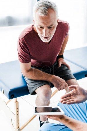 Photo pour Vue recadrée du docteur retenant la tablette numérique et faisant des gestes près du patient mûr - image libre de droit