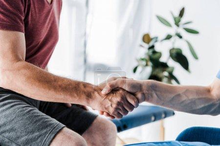 Foto de Vista recortada del médico estrechando las manos con el hombre - Imagen libre de derechos