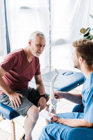Photo pour Patient heureux regardant le modèle de colonne vertébrale de fixation de docteur - image libre de droit