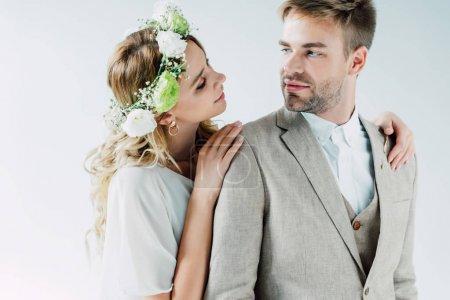 Photo pour Mariée attrayante et beau marié étreignant et regardant l'un l'autre - image libre de droit