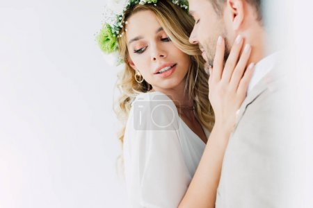 Photo for Attractive bride and handsome bridegroom hugging and looking away - Royalty Free Image