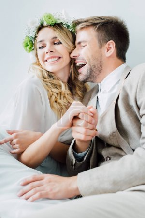Photo for Attractive bride and handsome bridegroom holding hands and looking away isolated on grey - Royalty Free Image