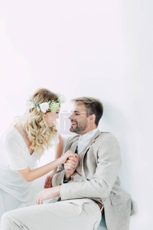 Photo for Attractive bride and handsome bridegroom holding hands and looking at each other - Royalty Free Image