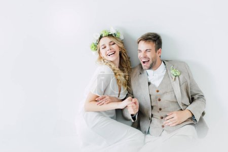 Photo for Attractive bride and handsome bridegroom holding hands and looking away - Royalty Free Image