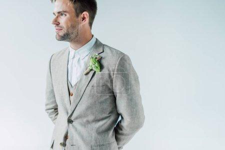 Photo pour Beau marié en costume avec boutonnière florale regardant isolé sur le gris - image libre de droit
