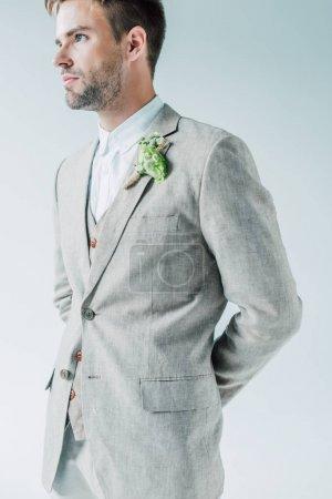 Photo pour Beau marié en costume avec boutonnière florale regardant loin isolé sur gris - image libre de droit