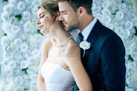 Photo for Attractive bride and handsome bridegroom hugging with closed eyes - Royalty Free Image