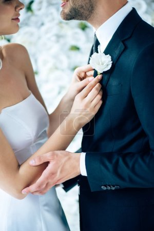 Photo for Cropped view of bride in wedding dress holding buttonhole of her bridegroom - Royalty Free Image