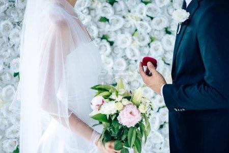 Photo pour Vue de côté de l'époux faisant la proposition à la mariée dans la robe de mariage - image libre de droit