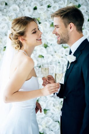 Photo for Attractive bride and handsome bridegroom smiling and clinking with champagne glasses - Royalty Free Image