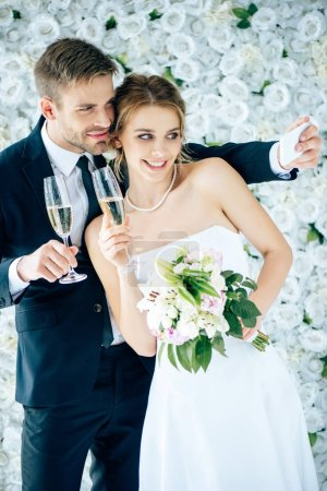 Photo for Attractive bride and handsome bridegroom smiling and taking selfie - Royalty Free Image