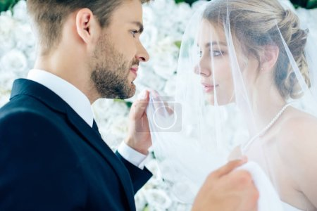 Photo for Side view of attractive bride and handsome bridegroom looking at each other - Royalty Free Image