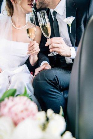 Photo pour Vue recadrée de mariée et marié baisers et cliquetis avec des verres de champagne - image libre de droit