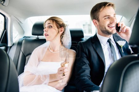 Photo for Attractive bride looking away and handsome bridegroom talking on smartphone - Royalty Free Image