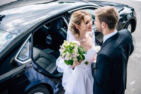 Bräutigam im Anzug küsst attraktive und blonde Braut mit Strauß