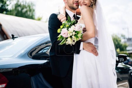 Photo for Cropped view of bridegroom in suit hugging bride in wedding dress with bouquet - Royalty Free Image