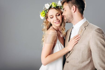 Photo for Handsome bridegroom in suit hugging with bride in wedding dress and wreath isolated on grey - Royalty Free Image
