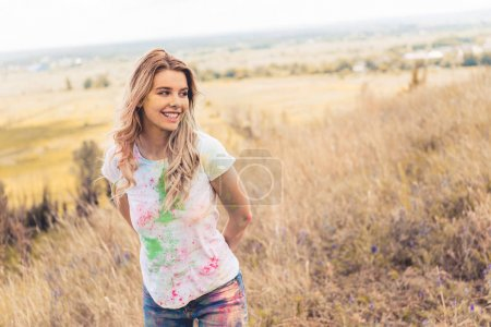 Foto de Mujer atractiva en la camiseta sonriendo y mirando hacia fuera - Imagen libre de derechos