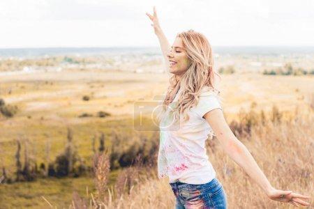 Foto de Mujer atractiva en la camiseta con las manos extendidas sonriendo y mirando hacia otro lado - Imagen libre de derechos