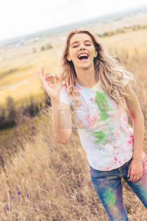 Photo for Attractive woman in t-shirt smiling and showing ok gesture - Royalty Free Image