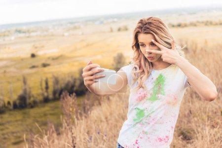 Photo pour Femme attirante dans le t-shirt prenant le selfie et affichant le signe de paix - image libre de droit