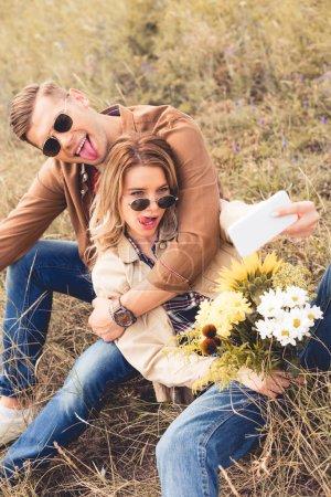 Photo pour Femme attirante avec le bouquet et l'homme beau prenant le selfie - image libre de droit