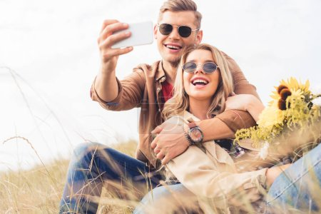 Photo for Attractive woman with bouquet and handsome man taking selfie - Royalty Free Image