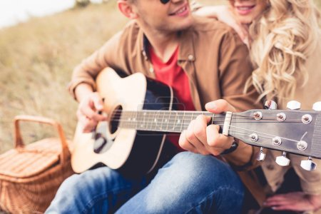 selective focus of man playing acoustic guitar and woman hugging him