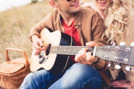 Photo pour Mise au point sélective de l'homme jouant de la guitare acoustique et la femme l'embrassant - image libre de droit