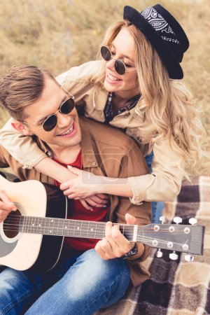 Photo for Handsome man playing acoustic guitar and attractive woman hugging him - Royalty Free Image