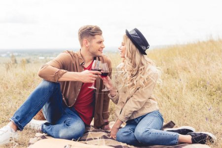 Photo for Handsome man and attractive woman clinking with wine glasses - Royalty Free Image