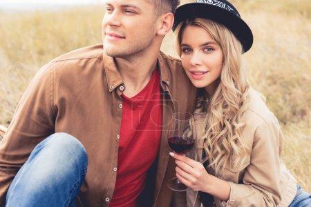 Photo pour Bel homme regardant loin et femme attrayante dans le chapeau tenant verre de vin - image libre de droit