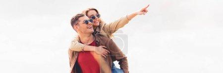 Photo pour Plan panoramique de bel homme piggyback sa copine attrayante et blonde - image libre de droit