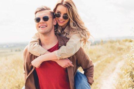 Photo pour Bel homme piggyback son attrayant et blonde copine à l'extérieur - image libre de droit