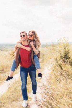 Photo pour Bel homme piggybacking sa petite amie attrayante et blonde à l'extérieur - image libre de droit