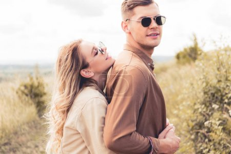 Photo for Attractive and smiling woman hugging handsome man in sunglasses - Royalty Free Image