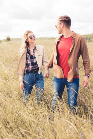 Photo for Attractive woman and handsome man in sunglasses holding hands - Royalty Free Image