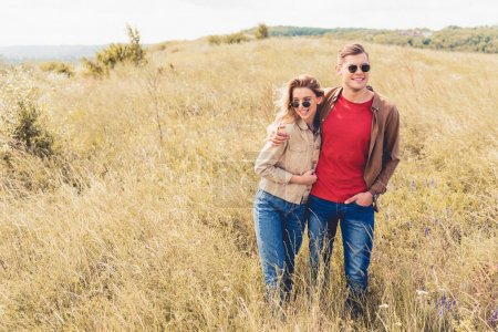Photo for Attractive woman and handsome man in sunglasses hugging outside - Royalty Free Image