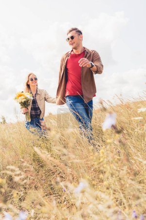 Photo for Attractive woman and handsome man in sunglasses walking and holding hands - Royalty Free Image